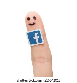 BELCHATOW, POLAND - AUGUST 31, 2014: Facebook logo printed on paper and stuck to the finger.