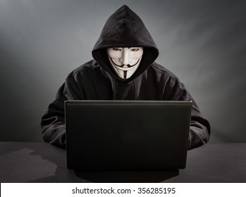 Belchatow, Poland - December 18, 2015: Man with the laptop wearing Vendetta mask - symbol for the online hacktivist group Anonymous. Black background.