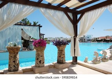 Belek, Turkey - June 01, 2015: The stylish tents, original  flower vases, blue pool in hotel Ela Quality Resort.