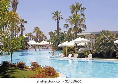 BELEK, TURKEY - JUNE 14, 2015: Summer view of SuSeSi Luxury Resort Hotel with tourists in swimming pool in Belek, Turkey.