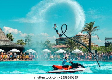 Belek, Turkey - September 12, 2018. Exciting fly board watershow at the pool party on a sunny summer day. A man is doing acrobatics with flyboard attached to jet ski with spectators on the back.