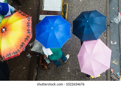 Belem do Para, Brazil - February 03, 2018: Top view of unidentified people on the street during an amazonian rainy season day with colorful umbrellas