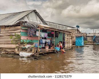 Belen, Peru- March 27, 2018: Family doing laundry in the river.  Floating houses in the floodplain of the Itaya River, poorest part of Iquitos - Belén. Venice of Latin America.Region Loreto, Peru.