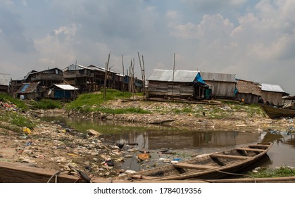 Belen,Iquitos, Peru - March 27, 2018: Wooden boat between huge pollution on the river Itaya, next to the Belen market, during the low water. Amazonia. Amazon.