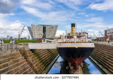 Belfast, Antrim, Northern Ireland, UK - April 25, 2018: SS Nomadic, tender to the liner Titanic, has been restored and sits in Hamilton Dock. The Titanic Belfast building is in the background