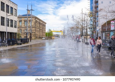 Belfast, Antrim, Northern Ireland, UK - April 25, 2018: Fountains in St. Anne's Square. The Custom House is to the left and a Harland and Wolff shipyard crane can be seen in the distance.
