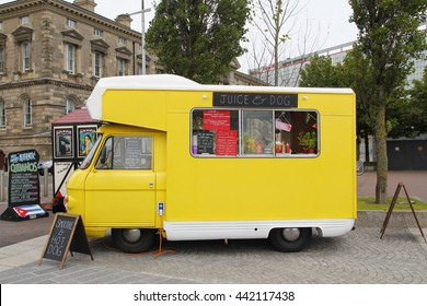 BELFAST, IRELAND - AUGUST 08, 2015: Yellow food truck of natural fruit juice and veggie food parked in the street, waiting for costumers at  the city of Belfast in Northern Ireland, on August 08, 2015
