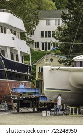 BELFAST, MAINE/USA - SEPTEMBER 18, 2017: A worker cleans the hull of a large yacht in Front Street Shipyard near a residential area in this coastal community and travel destination.
