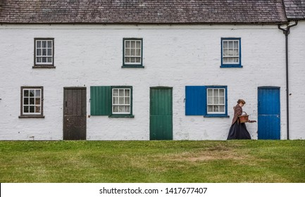 BELFAST, NORTHERN IRELAND  - JULY 31: Woman in period costume walking in front of 19th Century row houses. September 31, 2018 in Belfast, Northern Ireland.