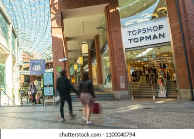 BELFAST, NORTHERN IRELAND- MAY, 2018: A shopping couple walking in to Topshop / Topman shopping store in Belfast's Victoria Square shopping centre