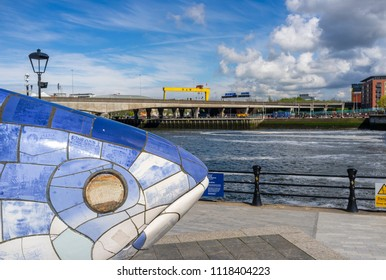 Belfast, Northern Ireland, UK - April, 28, 2018: The Big Fish, Donegall Quay. One of the giant Harland and Wolff Shipyard cranes can be seen in the distance.