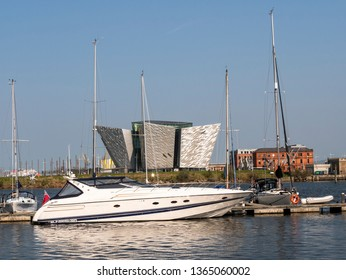 Belfast, Northern Ireland, UK - April 8, 2019: A Sunseeker cruiser moored in Belfast Harbour Marina with Titanic Belfast in background. Titanic Hotel is on the right.