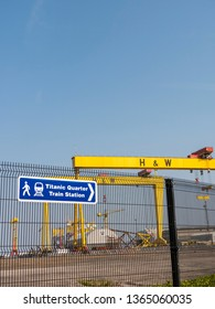 Belfast, Northern Ireland, UK - April 8, 2019: Sign to Titanic Quarter Train Station with Harland and Wolff shipyard cranes Samson and Goliath in background