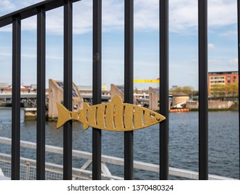 Belfast, Northern Ireland, UK - April 13 2019: Railings with Lagan Weir in the background. Shipyard crane can be seen in the distance