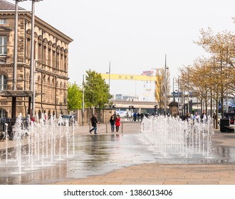 Belfast, Northern Ireland, UK - April, 18, 2019: People in Queen's Square near the fountains. Harland and Wolff Shipyard cranes can be seen in the distance