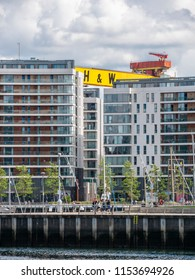 Belfast, Northern Ireland, UK - August, 8, 2018: Apartments, Titanic Quarter with one of the Harland and Wolff Shipyard cranes