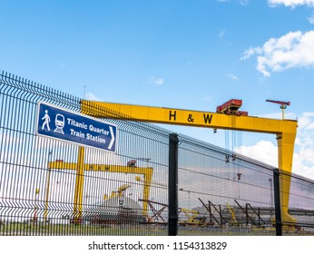 Belfast, Northern Ireland, UK - August, 8, 2018: Sign to Titanic Quarter Train Station. The two giant Harland and Wolff cranes can be seen in the background