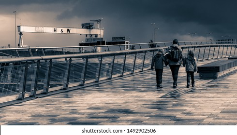 BELFAST, NORTHERN IRELAND / UK - AUGUST 18, 2019 - Tourists walk on pedestrian bridge over River Lagan while Harland and Wolff's crane Goliath is draped in a Save Our Yard banner