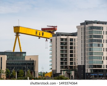 Belfast, Northern Ireland, UK - August 24, 2019: The giant Harland and Wolff Shipyard cranes tower over nearby offices and apartment blocks in Titanic Quarter