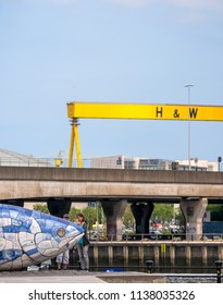 Belfast, Northern Ireland, UK - July, 13, 2018: People examine the Big Fish with one of the giant Harland and Wolff cranes visible in the background