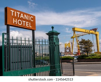 Belfast, Northern Ireland, UK - July, 30, 2018: Titanic Hotel sign with Harland and Wolff Shipyard crane in background