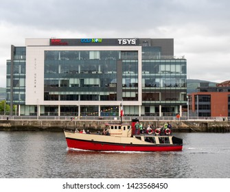 Belfast, Northern Ireland, UK - June 13, 2019: Titanic Tour boat, Mona, sails past the City Quays 1 building, Donegall Quay