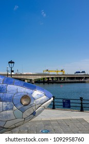 Belfast, Northern Ireland, UK - May, 17, 2018: The Big Fish is a 10 metre long sculpture by John Kindness in Donegall Quay.  Harland and Wolff cranes can be seen in the distance