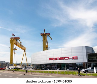 Belfast, Northern Ireland, UK - May 14, 2019: Porsche dealership, Titanic Quarter with Harland and Wolff cranes Samson and Goliath in background