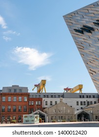Belfast, Northern Ireland, UK - May 14, 2019: Titanic Hotel with section of Titanic Building in foreground and shipyard cranes, Samson and Goliath in background.