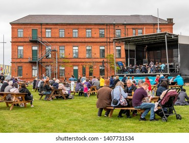 Belfast, Northern Ireland, UK - May 25, 2019: Belfast Titanic Maritime Festival in Titanic Quarter. Pupils from City of Belfast School of Music play with Titanic Hotel in the background