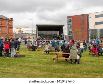 Belfast, Northern Ireland, UK - May 25, 2019: Belfast Titanic Maritime Festival in Titanic Quarter. People relaxing and watching entertainment adjacent to Titanic Belfast Building