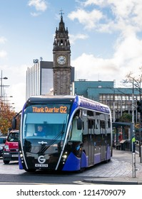Belfast, Northern Ireland, UK - October, 27, 2018: A Glider bus pulls away from a bus stop with the Albert Memorial Clock in the background