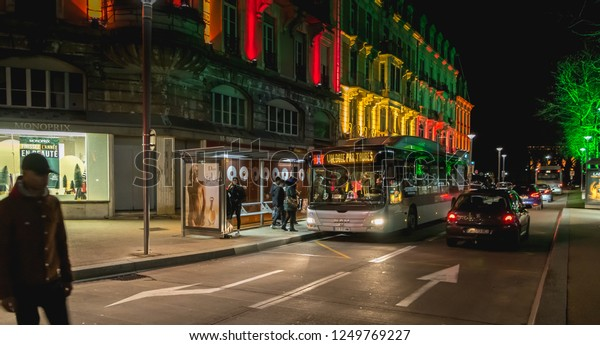 Belfort, France - December 26, 2017: People boarding a shuttle bus at a stop at a bus station that goes around the Christmas market on a winter day