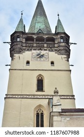Belfry of gothic cathedral of Saint Nicholas in Presov with arched windows and porch under pointy roof. Clock on belfry wall uses Latin numerals.