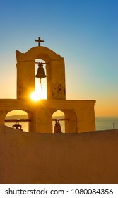 The belfry of a Greek orthodox church in Thira town in Santorini Island at sundown, Greece