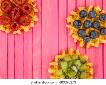 Belgian Butter Waffles With Blueberries Raspberries and Kiwi Fruit Against a Pink Wooden Background