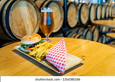 Belgian cheeseburger, French fries and beer with blurred wooden barrels in background