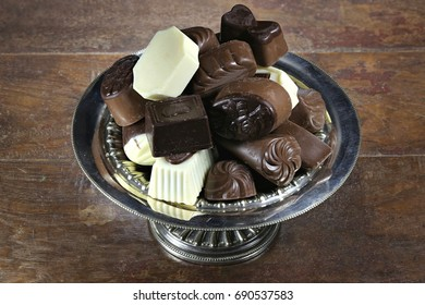 Belgian chocolate pralines in a silver bowl on rustic wooden background