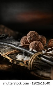 Belgian chocolate rum truffles shot against a festive, dark background with vintage wooden skis tied with twine rope with snowflakes. Generous accommodation for copy space.