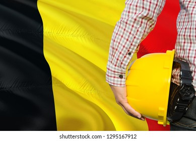 Belgian Engineer is holding yellow safety helmet with waving Belgium flag background. Construction and building concept.