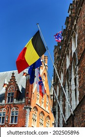 Belgian, European and Bruges flags waving on ancient building