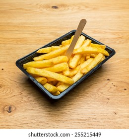 Belgian fries in a black shell on wooden background