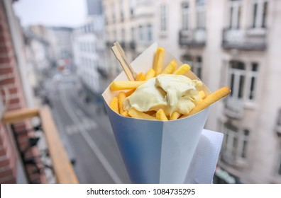 Belgian fries with mayonnaise on blurred Brussels street