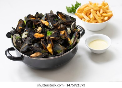 Belgian mussels and fries on white marble