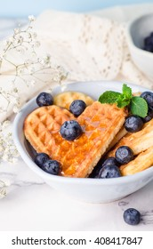 Belgian shape heart waffles with blueberries and honey on white marble background. Selective focus