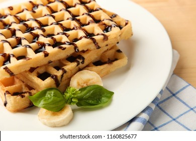 Belgian waffle with banana on wooden background. Concept dessert.
