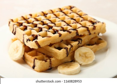 Belgian waffle in chocolate with banana on neutral background. Concept dessert.