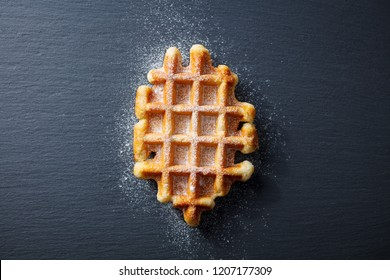 Belgian waffle with icing sugar. Slate background. Top view.