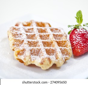 Belgian waffle with powdered sugar and a strawberry