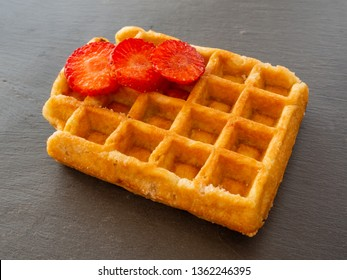 A Belgian waffle with strawberry pieces on a slate plate
